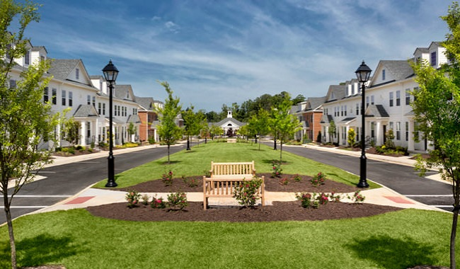 park bench on well manicured lawn in the middle of apartment community