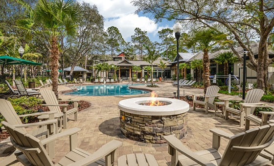 open fire place surrounded by lawn chairs near pool